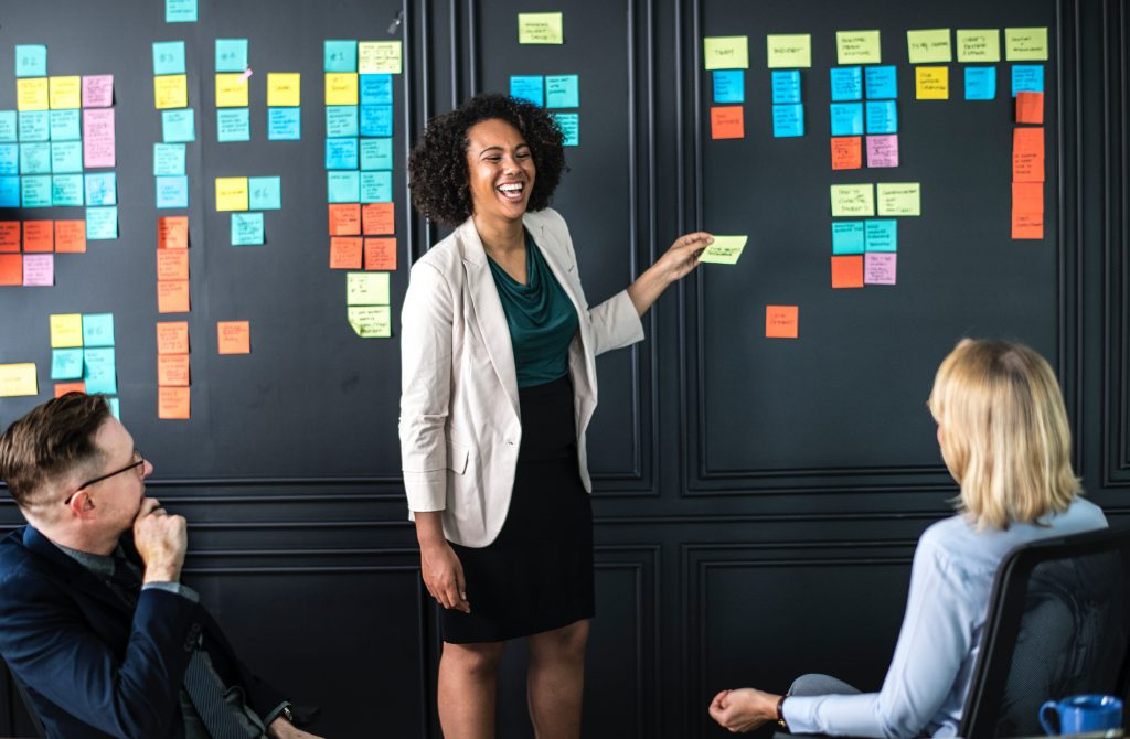 A person standing in front of a wall of post-it notes engaged in planning.