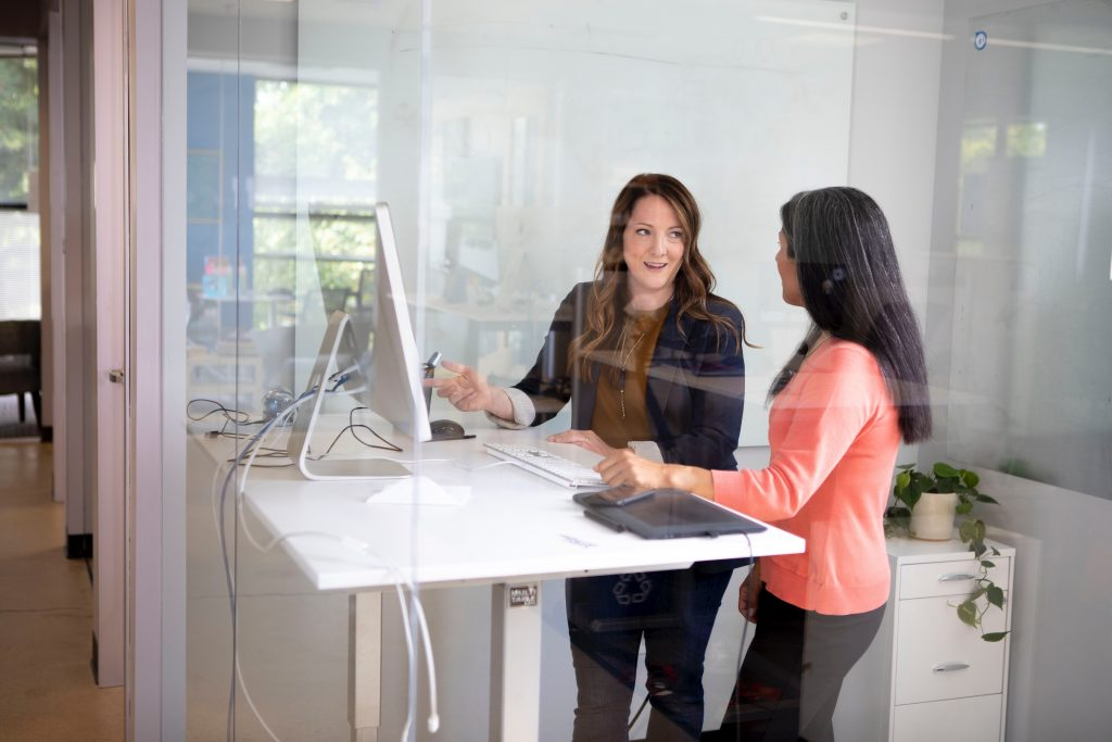 Two people participating in conversation at a computer.