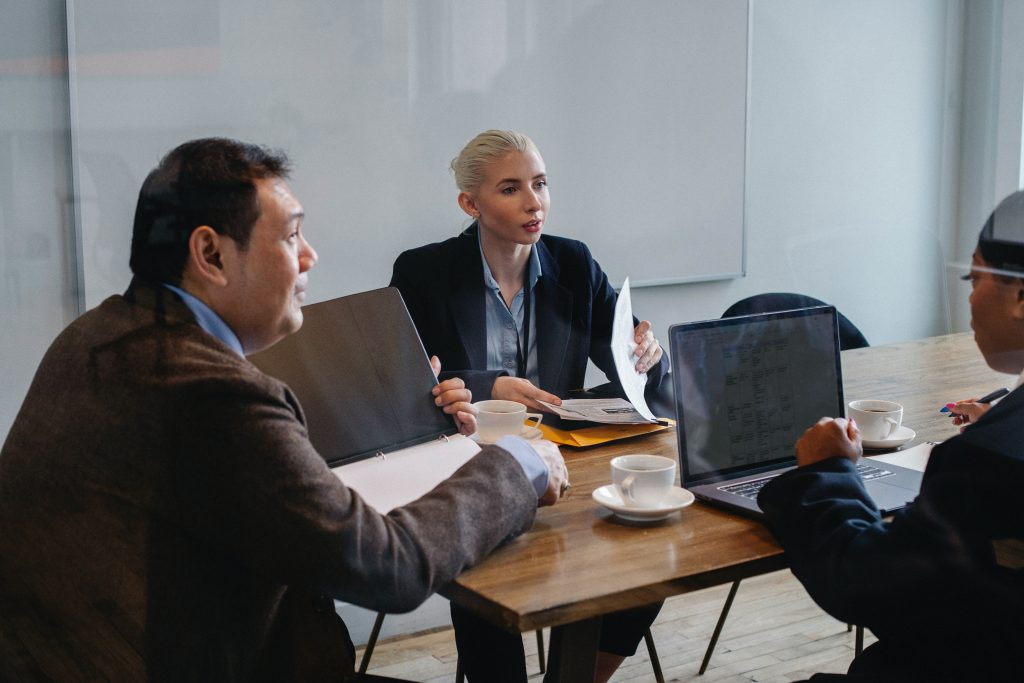 Three people seated at a table involved in a business meeting.