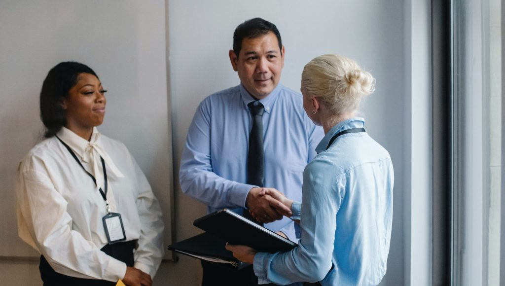 Three people standing in a business meeting.