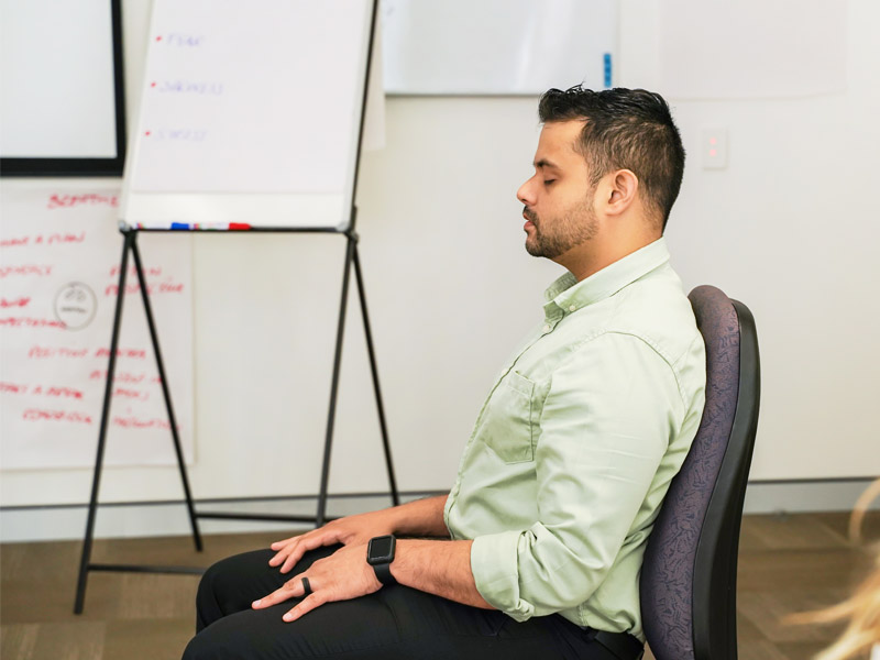 A person seated participating in a mindfulness activity.