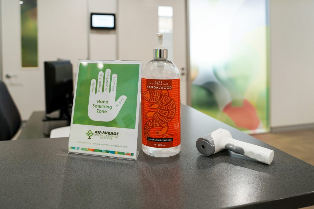 ATI-Mirage reception with COVID-19 hand sanitising zone sign, hand sanitiser and temperature checking device