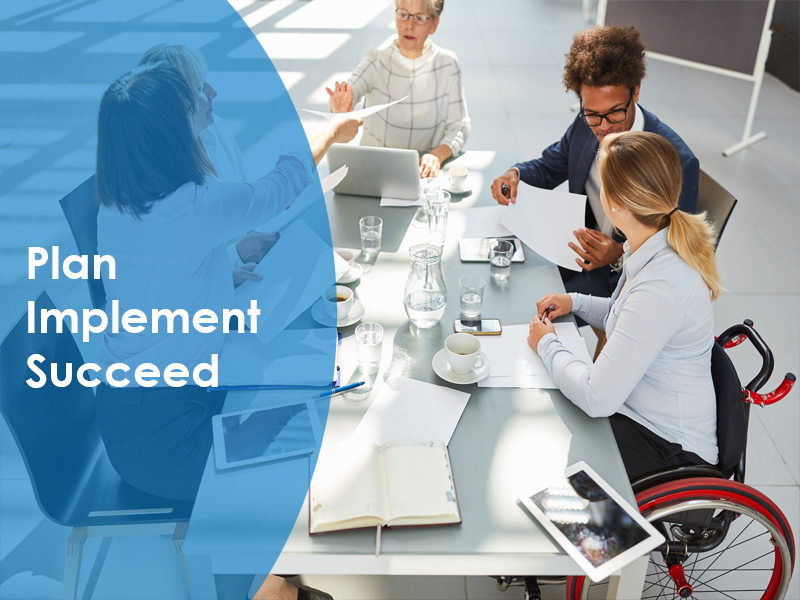 Five people sitting around the table discussing project management training with words of plan, implement, succeed written next to it